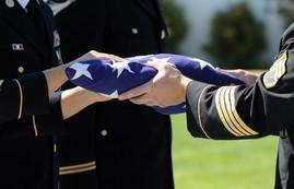 Military flag presentation ceremony at a Veteran's memorial