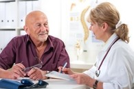 VA provider and Veteran meet to discuss patient information during rounding
