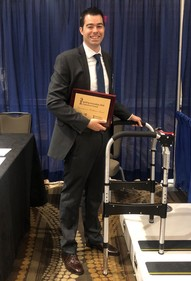 Biomedical engineer Kevin Foglyano with the self-leveling walker and award