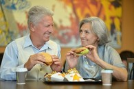 Senior couple eating fast food
