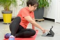 Veteran exercising with tablet, at home