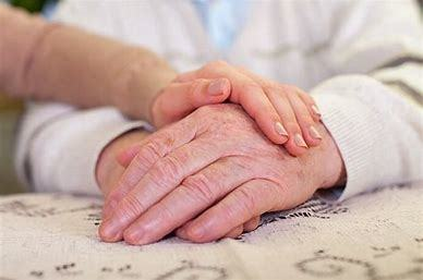 Image of elderly hands holding younger hands.