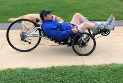man paralyzed from waist down riding a recumbent bike outside