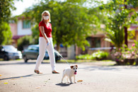 A Veteran with mask and her dog walking around the neighborhood