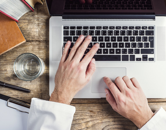 provider hands on laptop keyboard stethoscope to side
