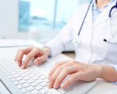 Provider sitting at computer with hands on keyboard