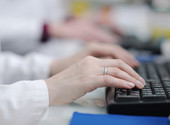 Medical personnel typing on keyboards