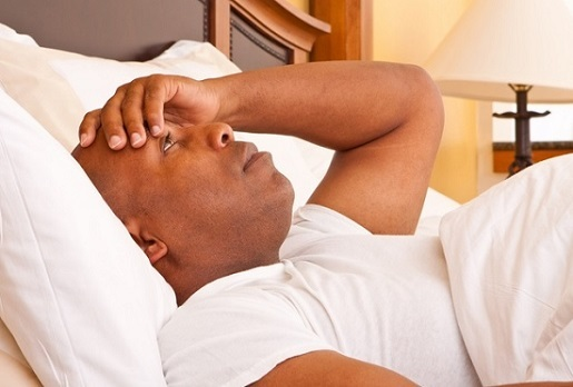 A man lays in bed staring at the ceiling, looking frustrated