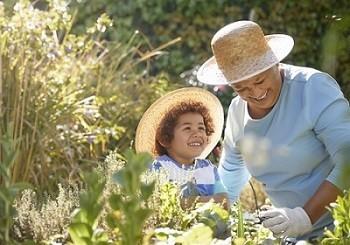 An older woman and her grandchild gardening among tall grass