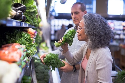 A woman smells leafy greens at the market with her partner