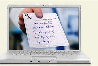 medical personnel holding prescription in computer screen