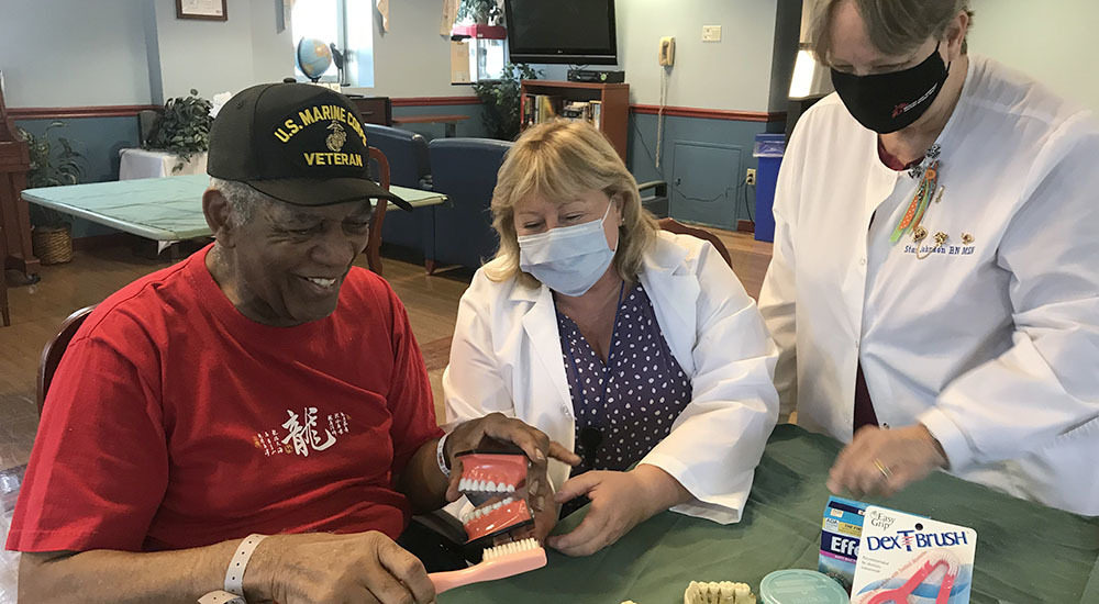 male Veteran and two physicians showcasing how to brush teeth