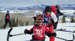 woman on ski equipment along with man behind pushing