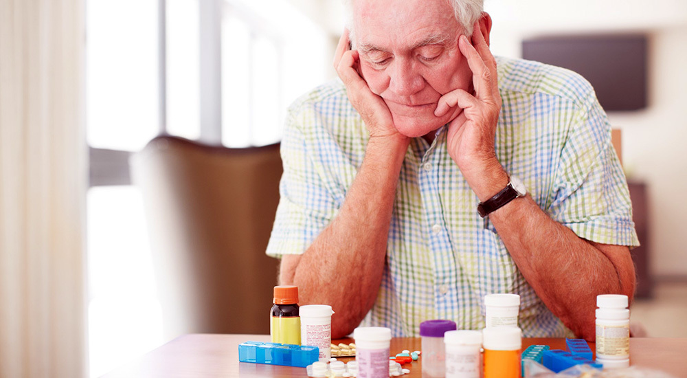 Elderly man looking at pill bottles on the table