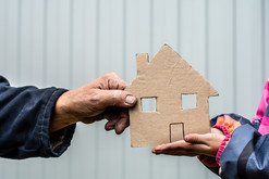 man and woman holding a cardboard cut out home