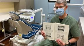 Dentist in dental operatory holding up scrapbook