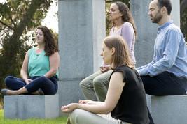 Four people sitting, meditating