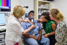 Three VA clinicians inspect a Veteran's procedure
