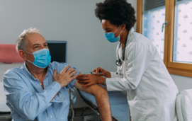 man receiving an injection from health care worker