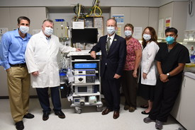 Six people standing next to medical device
