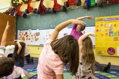 preschool children stretching with teacher