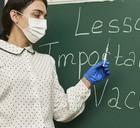 Woman teacher at blackboard on importance of vaccines