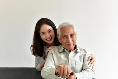 Photograph of young woman and her elderly grandfather looking into the camera smiling.