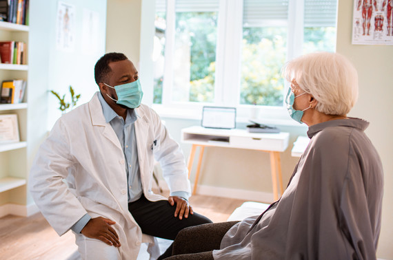 Photograph of doctor and patient having a conversation during an appointment. Both are seated and wearing face masks.
