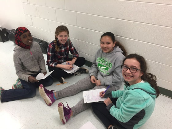 photo of 4 girls sitting on floor with paper and pencils