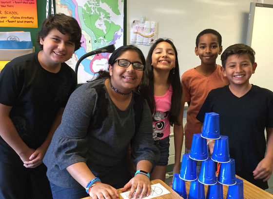 photo of students standing around cup game
