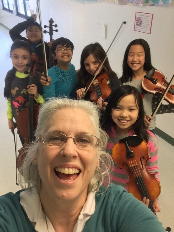 photo of students with violins and adult