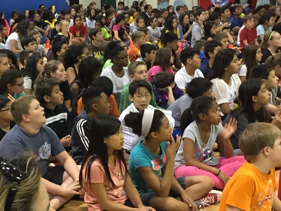 photo of many students seated on floor for concert