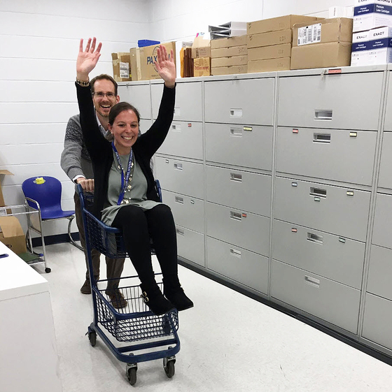 Bucknell ES staff members. One is pushing the other in a shopping cart for #NaitonalFunatWorkDay