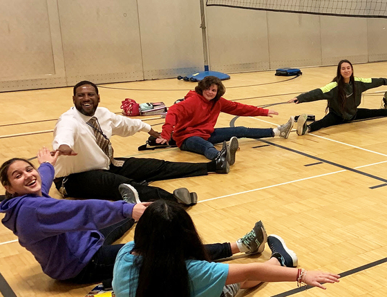 Frost MS Principal Anthony Harris stretching with students during a physical education class.