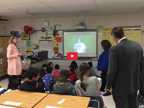 students in a classroom watching a flipvideo