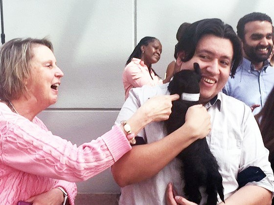 Functional Applications Specialist Michael Sanchez holds a puppy at Willow Oaks.