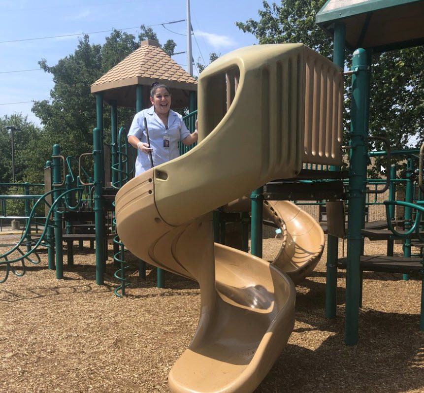 Rubia Ramos, custodian, Wolftrap ES, standing on a slide with a broom