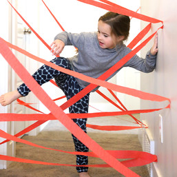 young girl moving through a maze of red paper tape strung across the home hallway.   laser maze game
