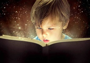 young boy reading a book. book is illuminated and shining on the boys face