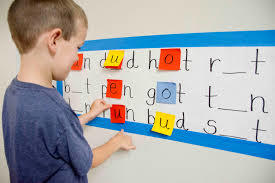 young boy working with letters on a wall chart at home