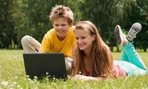 children looking at a laptop outside on the grass