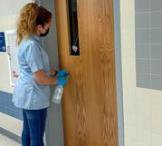 Custodian cleaning door handle.