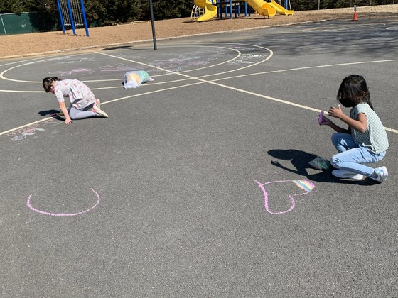 photo of children drawing with chalk on the playground