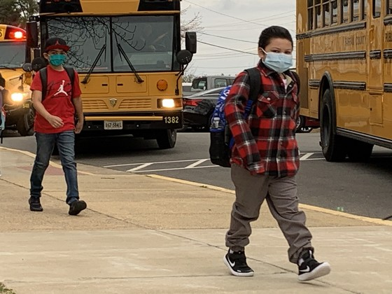 Photo of students walking from the bus into school