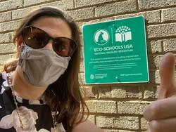 Melanie Meren in front of Eco-Schools plaque