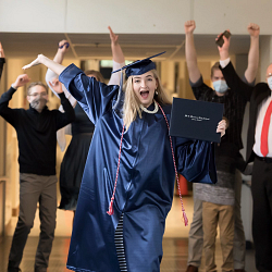 grad with arms up