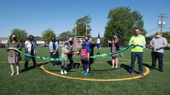 A group of adults stand in a semi-circle behind two children who cut a large ribbon with scissors.