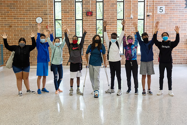 Group of students raising their arms.