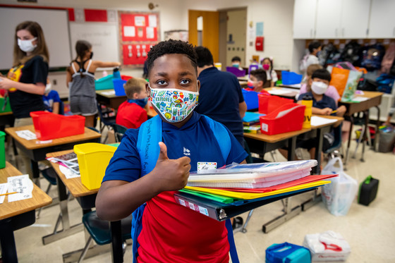 Student in mask giving a thumbs up.