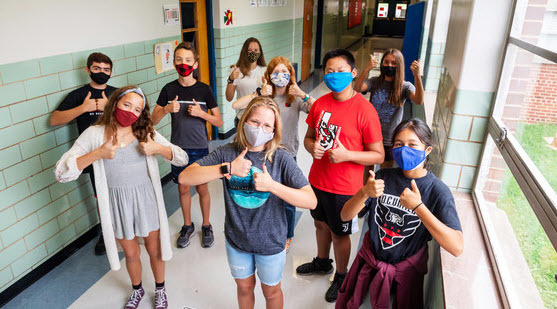 Masked students in hallway with thumbs up